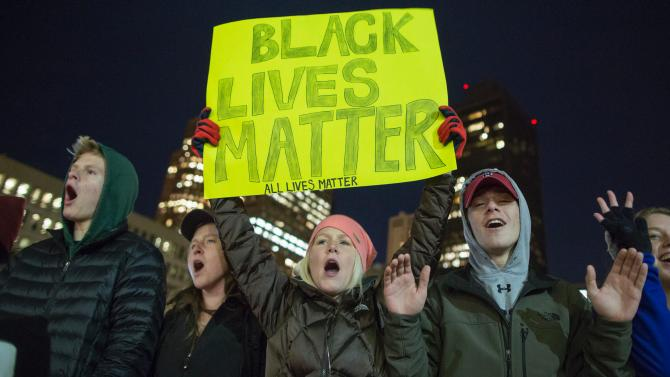 Demonstrators chant and hold signs in Boston City Hall Plaza on Dec. 4, 2014. Scott Eisen/Getty Images