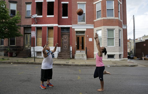 Children play with a basketball in front of a vacant home, left, and a restored home in the Reservoir Hill neighborhood of Baltimore on May 10, 2015. (AP Photo/Patrick Semansky)