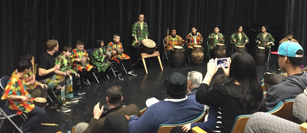 """Onlookers watch as the ZUMIX drum group of East Boston kicks off the third """"town hall"""" forum in the Boston Creates planning process. (Jeremy D. Goodwin for WBUR)"""